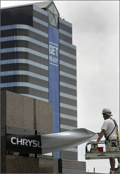 In this Aug. 4, 2007 file photo, sign installer Brian Bartkowiak reveals the new Chrysler sign after removing the DaimlerChrysler sign from in front of their headquarters in Auburn Hills, Mich. After running Chrysler LLC for a year, Cerberus Capital Management LP must be wondering if its mascot, the three-headed dog that guards the gates of hell, is protecting it from the underworld or leading it into the flames. (AP Photo/Jerry S. Mendoza, file)