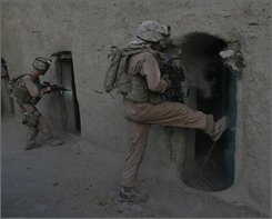 A U.S. Marine breaks the door of a house during patrol in the town of Garmser in Helmand Province of Afghanistan Wednesday, July 9, 2008.   The Pentagon has ordered roughly 1,250 Marines serving as trainers for the Afghan security forces to stay on the warfront about a month longer. (AP Photo/Rafiq Maqbool)