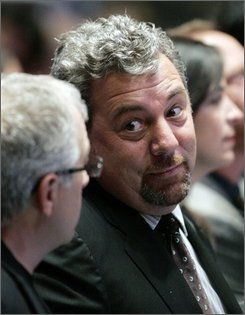 "** In this Nov. 4, 2007, file photo, Cablevision Systems Corp's. Chief Executive James Dolan watches the first half of an NBA game between the New York Knicks and the Minnesota Timberwolves in New York. Dolan said Tuesday, Aug. 5, 2008, the company is ""actively looking"" at options to close the gap between operating performance and the market value of its shares. The company plans to hire investment banking firms. (AP Photo/Jeff Zelevansky, file)"