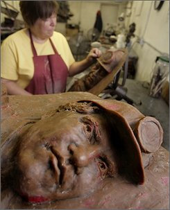 Karen Templeton makes some final touches to wax figures that will be turned into a bronze monument at a foundry Monday, July 21, 2008, in Lehi, Utah. Wednesday marks the one-year anniversary of a mine collapse outside of Huntington, Utah, that killed several coal miners and their rescuers. (AP Photo/Douglas C. Pizac)