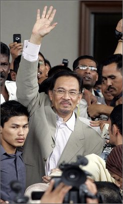 "Malaysian opposition leader Anwar Ibrahim waves as he leaves the Kuala Lumpur Sessions Court in Kuala Lumpur, Malaysia, Thursday, Aug. 7, 2008. Anwar pleaded innocent Thursday to a sodomy charge, dismissing it as a ""treacherous"" accusation, as he was freed on bail to campaign for a key by-election to Parliament. (AP Photo/Lai Seng Sin)"