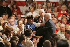 Republican presidential candidate Sen. John McCain, R-Ariz. gets a hug from disabled veteran Michael Haines, left, Thursday, Aug. 7, 2008, during a town hall meeting at the Veterans Memorial Civic and Convention Center in Lima, Ohio.  (AP Photo/Mary Altaffer)