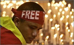 A Tibetan exile,  wearing a Free Tibet headband, re-lights blown out candles after a candle-lit vigil at a peaceful anti-China protest in New Delhi, India, Friday, Aug. 8, 2008. (AP Photo/Gurinder Osan)