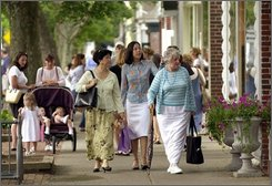 In this July 11, 2001 file photo, people window shop and stroll down a street in East Hampton, New York.  Strolling the sidewalks on a sunny summer afternoon, there would be little hint of the uproar brewing at East Hampton Town Hall.  But a downgrade in the town's credit rating by a major Wall Street agency amid a budget deficit that could pass $12 million is stirring calls by some for the ouster of the entire town board, particularly its three-term incumbent supervisor.  (AP Photo/Kathy Willens, File)