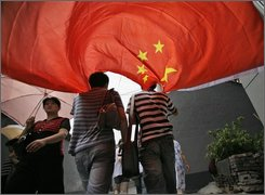 A Chinese flag floats as people proceed to the opening ceremony for the 2008 Olympic Games in Beijing in the National Stadium, known as the Bird's Nest, Friday, Aug. 8, 2008. (AP Photo/Oded Balilty)
