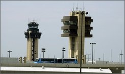 A Skylink tram passes in front control towers at the Dallas-Fort Worth International Airport, Sunday, Aug. 10, 2008, in Grapevine, Texas. Airlines are cutting flights under the pressure of rising fuel costs, and that means fewer passengers and less money from parking and food concessions at DFW. For the first time in its 34-year history, the airport is freezing its budget and rethinking future expansion plans. (AP Photo/Matt Slocum)