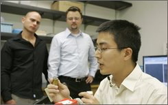 Jie Yao, right,  co-author of a new science paper, looks over a 3-D material that can bend visible light backwards as co-authors Guy Bartal, left, and Jason Valentine, center, look on during a news conference in a laboratory at the University of California at Berkeley in Berkeley, Calif., Monday, Aug. 11, 2008. Scientists say they are a step closer to developing materials that could render people and objects invisible.  Researchers have demonstrated for the first time they were able to cloak three-dimensional objects using artificially engineered materials that redirect light around the objects. The new work moves scientists a step closer to hiding people and objects from visible light, which could have broad applications, including military ones. (AP Photo/Eric Risberg)