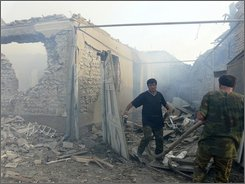 Emergency personnel  at work in front of buildings destroyed in an air raid  in the village of Tkviavi, Georgia, Monday, Aug. 11, 2008.  Russian armored vehicles rolled deep into central and western Georgia on Monday, quickly taking control of a key city, several towns and a military base, according to Georgian officials and witnesses. Georgia's president said Russian troops had effectively sliced his country in half. (AP Photo/David Nowak)