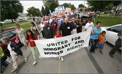 Hundreds of people march down a street, in a Sunday, July 27, 2008 file photo, in Postville, Iowa, during an immigration rally after a federal immigration raid of the local Agriprocessors plant in May, during which nearly 400 people were arrested. The kosher slaughterhouse is run by the Rubashkin family, who deny allegations that the company knowingly hired illegal immigrants and children and tolerated abusive conditions. (AP Photo/Charlie Neibergal, File)