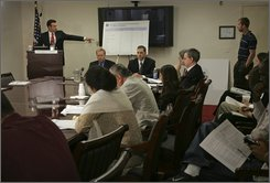 Congressional Budget Office (CBO) Director Peter Orszag, left, gestures during a briefing in Washington, Tuesday, Aug. 12, 2008, on a new study quantifying the budgetary cost and number of contractors supporting U.S activities in the Iraq. (AP Photo/Lawrence Jackson)