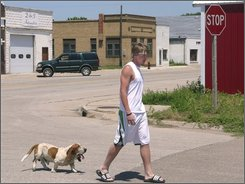 Charles Schuett, 17, and his basset hound Jake walk in downtown Maxwell,  Neb., with the long-closed Story's Hardware store seen on far right, July 16, 2008. The estimated, median size of Nebraska towns, 320, which is about the same estimated population of Maxwell, may be the smallest in state history.(AP Photo/Nate Jenkins)