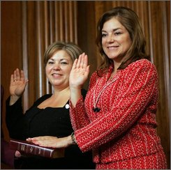 Sisters, Reps. Linda Sanchez, D-Calif., left, and Loretta Sanchez, D-Calif, pose during a re-enactment of their swearing-in ceremony on Capitol Hill in Washington, Jan. 4, 2007. In their new book, written with co-author Richard Buskin, the sisters alternate telling their stories, each in her own voice.(AP Photo/Susan Walsh, File)