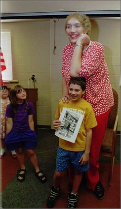 In this Sept. 2, 1995 file photo, Sandy Allen, poses for a picture with Will Denk, at the library in Shelbyville, Ind.  The 7-foot-7 Allen  considered the world's tallest woman died early Wednesday Aug. 13, 2008 at a nursing home in her hometown of Shelbyville. She was 53.  (AP Photo/Phil Meyers, File)