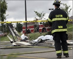 As an Easton firefighter watches, a chaplain from the Mansfield Fire Department says a prayer by the wreckage of a smoldering small plane that crashed in the parking lot of Hannaford's Supermarket in Easton, Mass., Tuesday, Aug. 12, 2008. Preliminary reports indicated that three people were killed in the crash of the plane, which was carrying a patient to Boston for medical treatment. (AP Photo/Robert Klein)