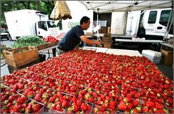 In this June 20, 2008 file photo, a man arranges boxes of strawberries at the Union Square Greenmarket  in New York. Consumer prices shot up in July at twice the expected rate, pushed higher by surging energy and food costs. The latest surge left inflation running at the fastest pace in 17 years. (AP Photo/Mark Lennihan, file)