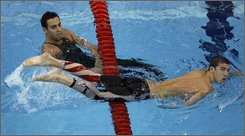 Michael Phelps of the United States, right, goes past Milorad Cavic of Serbia after Milorad won a heat of the men's 100-meter butterfly during the swimming competitions in the National Aquatics Center at the Beijing 2008 Olympics in Beijing, Thursday, Aug. 14, 2008. Phelps was placed second. (AP Photo/Greg Baker)