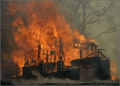 In this Oct. 23, 2008 file photo, a wildfire burns a house in Running Springs, Calif., Tuesday, Oct. 23, 2007. Faced with hundreds of big, hard-to-control blazes, California is struggling with what could be its most expensive wildfire season ever, burning through $285 million in the last six weeks alone and up to $13 million a day. (AP Photo/Marcio Jose Sanchez)