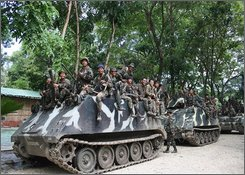 Philippine troops ride on tanks as they regain control of Pikit town, North Cotabato, southern Philippines from Muslim rebels on Thursday Aug. 14, 2008. Tensions in the southern Philippines , the traditional homeland of minority Muslims , peaked this week after government troops retook the farming villages from about 1,000 guerrillas who occupied the area last month. (AP Photo/Jeff Maitem)