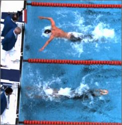 This first of three video frame grab images taken from International Olympic Committee Beijing Olympic Broadcasting pool video, shows United States swimmer Michael Phelps, above, as he swims toward the finish of the men's 100-meter butterfly, along side Serbia's Milorad Cavic in the adjacent lane. Phelps beat Cavic by a hundreth of a second setting an Olympic record in 50.58 seconds, earning his seventh gold medal and matching Mark Spitz's seven gold medals from the 1972 Munich Games. (AP Photo/IOC BOB, Pool)