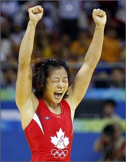 Canada's Carol Huynh celebrates her gold medal victory over Chiharu Icho from Japan in the women's freestyle 48 kilogram wrestling final at the Beijing 2008 Summer Olympics in Beijing, Saturday, August 16, 2008. (AP Photo/The Canadian Press, Paul Chiasson)