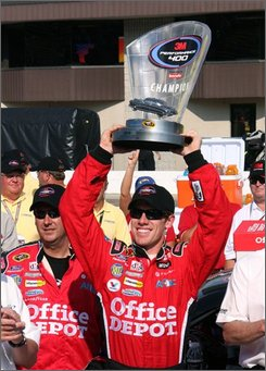 Carl Edwards holds up the trophy after winning the NASCAR 3M Performance 400 auto race at Michigan International Speedway in Brooklyn, Mich., Sunday, Aug. 17, 2008. (AP Photo/Carl Pendleton)