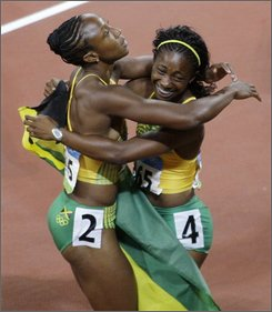 Jamaica's gold medal winner Shelly-Ann Fraser celebrates with her teammate Sherone Simpson, left, after the women's 100-meter final during the athletics competitions in the National Stadium  at the Beijing 2008 Olympics in Beijing, Sunday, Aug. 17, 2008. (AP Photo/Greg Baker)