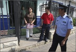 A Chinese police officer and a plain clothes security personnel, in red watch as Sun Liwei walk out of a Public Security Bureau where she tried to apply for a protest permit in Beijing, China, Monday, Aug. 18, 2008. A group of a dozen people tried to apply for permits to protest at one of three designated parks. Chinese authorities received 77 applications from people who wanted to hold protests during the Beijing Olympics, but all were withdrawn, suspended or rejected, state media said Monday. (AP Photo/Ng Han Guan)