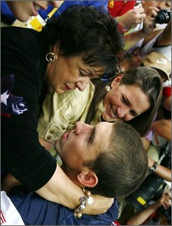Michael Phelps of the United States goes to hug his mother Debbie, left, as his sister, Hilary Phelps, looks on, after the medal ceremony for men's 4x100-meter medley relay final during the swimming competitions in the National Aquatics Center at the Beijing 2008 Olympics in Beijing, Sunday, Aug. 17, 2008. (AP Photo/Itsuo Inouye)