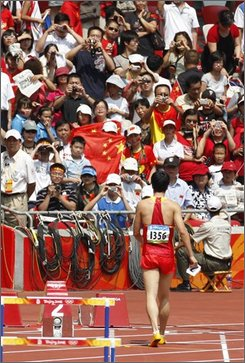 Spectators photograph China's Liu Xiang leaving the track after being injured in a men's 110-meter hurdles first round heat during the athletics competitions in the National Stadium  at the Beijing 2008 Olympics in Beijing, Monday, Aug. 18, 2008. (AP Photo/Kevin Frayer)