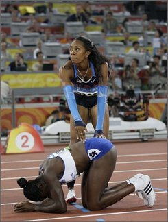 Britain's Christine Ohuruogu is congratulated by United States' Sanya Richards, bronze, after winning the gold in the women's 400-meter final during the athletics competitions in the National Stadium  at the Beijing 2008 Olympics in Beijing, Tuesday, Aug. 19, 2008. (AP Photo/David J. Phillip)