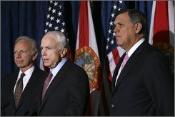 Republican presidential candidate Sen. John McCain, R-Ariz., center, flanked by Sen. Mel Martinez, R-Fla., right, and Sen. Joseph Lieberman, I-Conn., left, makes a statement to reporters after attending a business roundtable meeting, Monday, Aug. 18, 2008, at the Brevard Community College in Cocoa Beach, Fla.  (AP Photo/Mary Altaffer)