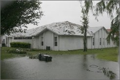 A home has roof damage from high winds brought by Tropical Storm Fay in Wellington, Fla. on Tuesday, Aug. 19, 2008. Flooding remained a concern as Fay heads up the Florida peninsula, with rainfall amounts forecast between 5 and 10 inches. The storm could also push tides 1 to 3 feet above normal and spawn tornadoes. (AP Photo/Jon Way)