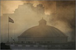 Smoke covers an Egyptian flag flying on top of the dome of the parliament building in Cairo, Egypt, Tuesday, Aug. 19, 2008. A large fire erupted Tuesday in Egypt's parliament, and five people were hospitalized for smoke inhalation, officials said. (AP Photo/Nasser Nasser)