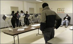 In this Nov. 7, 2006 file photo, two voters wait at right, as election workers gather trying to get the Diebold electronic voting machines up and running at the Garden Valley Neighborhood House in Cleveland. (AP Photo/Amy Sancetta, File)