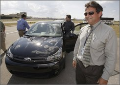 Ford Motor Company employee Andrew Sarkisian, right, smiles after driving a 2009 Ford Focus as other employees get their turn to test drive the vehicle at Ford's proving ground in Dearborn, Mich., Monday, Aug. 18, 2008. As Ford faces perhaps the most difficult period of its history, the company is trying to boost employee confidence by showing them, and letting them drive, the vehicles it hopes will pull the automaker out of a sales slump.   (AP Photo/Paul Sancya)