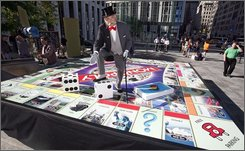 "In this photo provided by Hasbro, ""Mr. Monopoly"" stands on a large version of the global game board of the new ""Monopoly Here & Now"