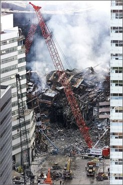 In this Sept. 18, 2001 file photo, a red crane looms over the smoldering wreckage of World Trade Center Building 7 in New York. Federal investigators said Thursday they have solved one of the undying mysteries of the Sept. 11, 2001 attacks