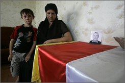 Angelina Valiyeva, 44, her son Irbek, stand by a portrait of her husband Garik, who was killed during an assault on the town by Georgians in Tskhinvali, Georgia, Friday, Aug. 22, 2008. When Georgian rockets came pouring down on this sleeping capital of the breakaway province of South Ossetia, Valiyeva and her family ran to a century-old synagogue. For four days, she and several dozen residents hid in its dark basement with scarce food and water, cupping their hands around the mouths of their terrified children when Georgian soldiers approached. (AP Photogia/Dmitry Lovetsky)