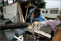George Sweat, 46, searches for his valuables after a large pine tree fell on his home, as girlfriend Peggy Mash, 53, played on her couch with her two cats, at right, during Tropical Storm Fay Friday, Aug. 22, 2008 in Hawthorne, Fla.  Residents of the Ranch Motel RV Park and Campground  rushed to save the woman, comforting her until rescue crews arrived. Mash was taken to the hospital with non-life threatening injuries.  (AP Photo/Doug Finger/The Gainesville Sun)