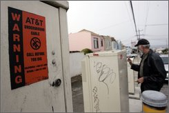 David Crommie, president of the Cole Valley Improvement Association, looks at an AT&T U-Verse utility box in San Francisco, Tuesday, Aug. 19, 2008. The box to the left, with warning label, is an  AT&T serving area interface (SAI) box (AP Photo/Paul Sakuma)