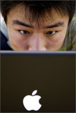 In this July 19, 2008 file photo, a customer looks at a computer in Beijing's newly-opened Apple computer store.  Customers in China of Apple Inc.'s iTunes online music store were unable to download songs since Monday, Aug. 18, 2008 and an activist group said Beijing was trying to block access to a new Tibet-themed album. (AP Photo/Oded Balilty, File)