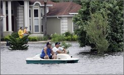 Residents in boat survey neighborhood flood damage from Tropical Storm Fay in Debary, Fla., Friday, Aug. 22, 2008. Tropical Storm Fay hobbled across Florida for a fifth day Friday as the state's death toll rose to five, while residents began plodding through muddy water to assess the flood damage to their homes. (AP Photo/John Raoux)