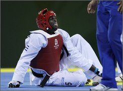 Cuba's Angel Valodia Matos sits on the mat with an injury during a bronze medal match against Kazakhstan's Arman Chilmanov for the men's taekwondo +80 kilogram class at the Beijing 2008 Olympics in Beijing, Saturday, Aug. 23, 2008. Matos attacked the official, throwing punches and kicks, after being declared the loser in his bronze medal match. He questioned the call when he was declared the loser of the match for taking too much injury time after he hurt his leg. (AP Photo/Matt Dunham)