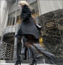 In this Wednesday Feb. 27, 2008, file photo two women pass the entrance to the American International Building in New York's Financial District. Stocks sank in light trading Monday, Aug. 25, 2008, as worries about American International Group Inc. touched off broader concerns that the deterioration of the credit markets will bring more big losses for financial companies. New York-based AIG was the steepest decliner among the 30 stocks that make up the Dow industrials. (AP Photo/Richard Drew, File)