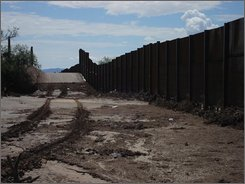 In this photo provided by the National Park Service, flooding around border fencing at the border of Lukeville, Ariz. and Sonoyta, Mexico is seen on July 12, 2008. Environmentalists say flooding caused by a newly built border security fence during a July monsoon bears out their concerns and warnings about the adverse environmental impacts of the government's rush to build fences. (AP Photo/Courtesy of the National Park Service)