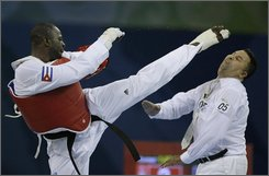 Cuba's Angel Valodia Matos, left, kicks match referee Sweden's Chakir Chelbat in the face during a bronze medal match against Kazakhstan's Arman Chilmanov in the men's taekwondo +80 kilogram class at the Beijing 2008 Olympics in Beijing, Saturday, Aug. 23, 2008. Matos attacked the official, throwing punches and kicks, after being declared the loser in his bronze medal match. (AP Photo/Matt Dunham)