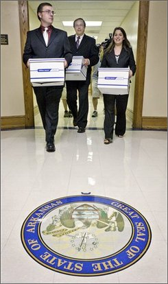 David Cox, left, and Jill Davis, right, carry boxes of petitions with Arkansas Family Council Action Committee President Jerry Cox, center, at the Arkansas state Capitol in Little Rock, Ark., Thursday, Aug. 21, 2008. The supporters of a proposal that would ban unmarried couples living together from adopting or fostering children turned in another 31,012 signatures Thursday in the hopes of placing the measure on the November ballot. (AP Photo/Danny Johnston)