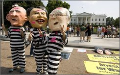 In this July 26, 2008 file photo, members of the Code Pink don masks of President Bush, left to right, Secretary of State Condoleezza Rice and Vice President Dick Cheney in prison outfit in front of the White House, to express their protest on the war on Iraq  in Washington.  (AP Photo/Manuel Balce Ceneta, File)