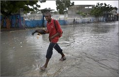 "A man, carrying a rooster, walks through a flooded street during heavy rains caused by Hurricane Gustav in Port-au-Prince,Tuesday, Aug. 26, 2008. Gustav barreled into Haiti toppling trees, dumping rain and sending fuel prices soaring on fears the storm could become ""extremely dangerous"" when it reaches the Gulf of Mexico. (AP Photo/Ariana Cubillos)"