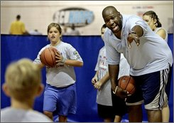 In this July 27, 2006 file photo, former NBA player Wayman Tisdale gives pointers to children at a Jr. NBA/Jr. WNBA basketball camp in Oklahoma City. The 44-year-old Tisdale, now an award winning jazz musician, had part of his right leg amputated Monday, Aug. 25, 2008 because of bone cancer. (AP Photo, File)